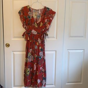 Floral jumpsuit with adjustable tie sides.